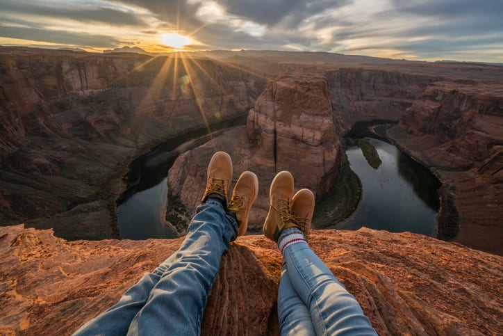 Personal perspective of two people relaxing on top of Grand Canyon