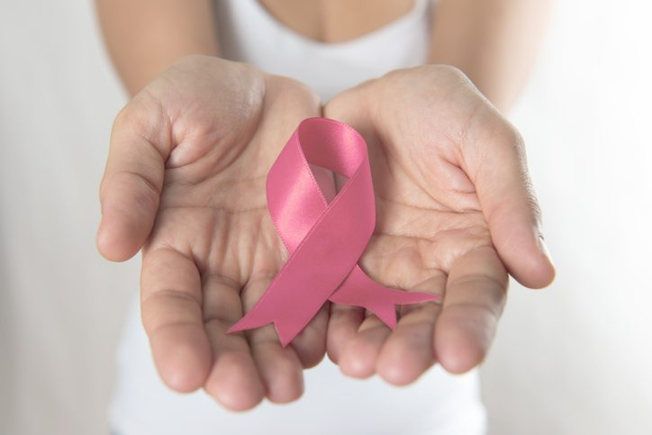 Woman holding Breast Cancer Awareness Ribbon in hands